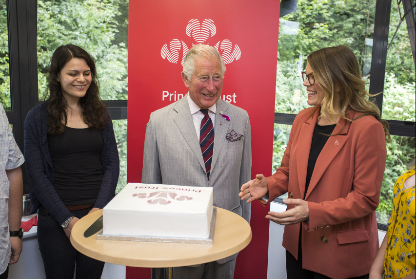 HRH Prince Charles being presented with a cake with Princes Trust logo on the top